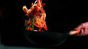 Chef tossing flaming pan of peppers