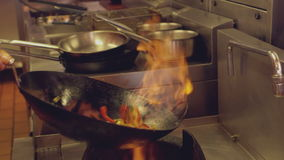 Chef tossing flaming stir fry stock video footage
