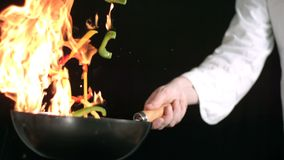 Chef tossing stir firy. Chef tossing stir fry in flaming wok in slow motion stock footage