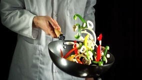 Chef tossing vegetable stir fry in wok stock footage