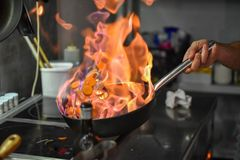 Chef tossing vegetables flambe in a pan over the burner royalty free stock image