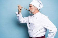 Chef trying meal. Confident mature chef in white uniform trying eating from wooden spoon and standing against blue. Background stock photo