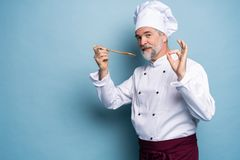 Chef trying meal. Confident mature chef in white uniform trying eating from wooden spoon and standing against blue. Background royalty free stock photos