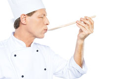 Chef trying meal. Side view of confident mature chef in white uniform keeping eyes closed while trying eating from wooden spoon and standing against white royalty free stock photos