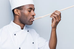 Chef trying meal. Side view of confident young African chef in white uniform keeping eyes closed while trying eating from wooden spoon and standing against grey Stock Photos