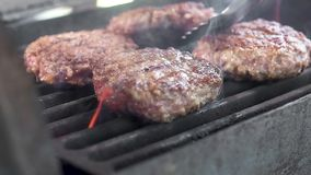 The chef turns the meat for a burger on the grill. Juicy meat is prepared on high heat. Lots of smoke. Close up.  stock footage
