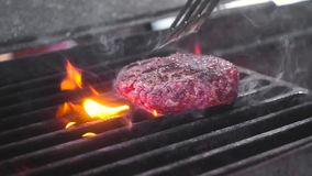 Chef turns the raw meat for the Burger on the hot grill. Lots of fire and smoke. Close-up, slow motion. Chef turns the raw meat for the Burger on the hot grill stock video footage