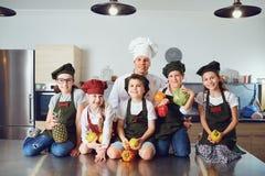 Chef und Kinder mit Gemüse in der stilvollen Küche lizenzfreies stockbild