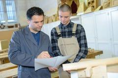 Chef und Lehrling, die in der Tischlerwerkstatt arbeiten stockfotografie