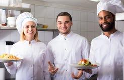 Chef und seine Assistenten, die Mahlzeit vorbereiten stockfotografie