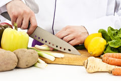 Chef in uniform cuts the vegetables Stock Photography