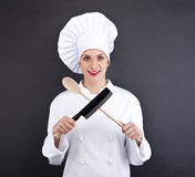 Chef in uniform holding a kitchen knife and spoon Stock Photography