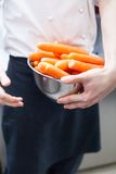 Chef in uniform preparing fresh carrot batons Royalty Free Stock Photos