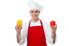 Chef in uniform showing capsicums Royalty Free Stock Photo