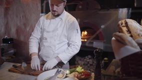 Chef in white rubber gloves cut vegetables cherry tomatoes, onion with big knife and put them in bowl with fish and. Chef in uniform and white rubber gloves cut stock footage