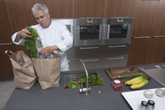 Chef Unpacking Groceries From Paper Bags In Kitchen Royalty Free Stock Image