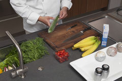 Chef Unwrapping Cucumber At Kitchen Counter Stock Photography