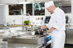Chef using brush to prepare a dish in the kitchen Stock Images