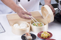 Chef using chopsticks hold Chinese dumpling Royalty Free Stock Photos