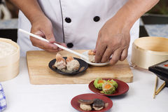 Chef using chopsticks hold Chinese dumpling Royalty Free Stock Image