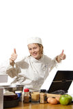 Chef using computer with thumbs up. A young female cook dressed in chef's uniform is cheering as she finds information on internet required for cooking Royalty Free Stock Photo