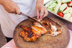 Chef are using Kitchen knife chicken grilled on wood block Stock Photography