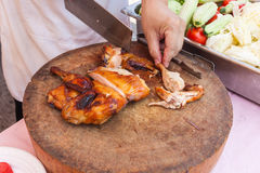 Chef are using Kitchen knife chicken grilled on wood block Stock Photos