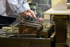 Chef using a metal press to prepare a hamburger patties. Deep fryers on front Royalty Free Stock Images
