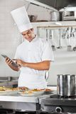 Chef Using Tablet With Pasta Dishes At Counter. Male chef using digital tablet with pasta dishes at commercial kitchen counter Stock Photography