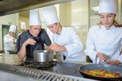 Chef vérifiant des cuisiniers de stagiaire de travail images stock