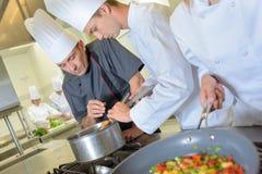 Chef vérifiant la nourriture de casserole du ` s de stagiaire images stock