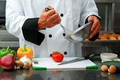 Chef with vegetables. Caucasian chef mixing something in a bowl with fresh vegetables on a cutting board in front of him in a restaurant kitchen stock image
