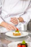 Chef verzieren Nachtischkuchen mit Erdbeere Lizenzfreie Stockfotos