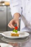 Chef verzieren Nachtischkuchen mit Erdbeere Lizenzfreie Stockfotografie