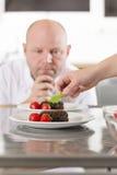 Chef verzieren Nachtischkuchen mit Erdbeere Stockfotos