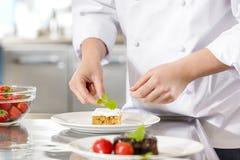 Chef verzieren Nachtischkuchen mit Zitronenblatt Stockfotografie
