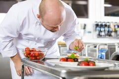 Chef verziert Nachtischkuchen mit Erdbeere in der Küche Stockfotos