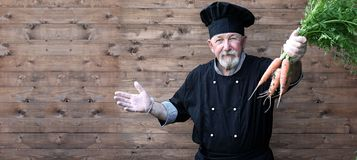Chef vieux dans l'uniforme avec des légumes Photographie stock