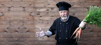 Chef vieux dans l'uniforme avec des légumes Photo libre de droits