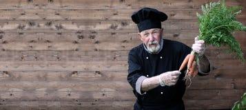 Chef vieux dans l'uniforme avec des légumes Photo stock