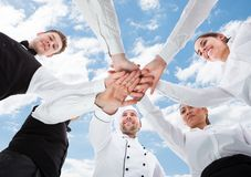 Chef and waiters piling hands against sky Stock Photo