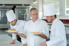 Chef watching trainees at work royalty free stock photo