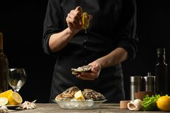 Chef watering raw oyster with lemon juice, with dry Italian wine, for cooking and cooking on a black background, Concept menu,. Cooking recipes, restaurant stock photo