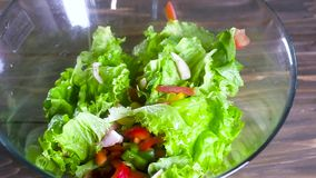 Chef watering salad with olive oil. a thin stream of oil pours on top of a fresh salad of natural vegetables in a large glass Cup. Healthy diet food. slow stock video footage