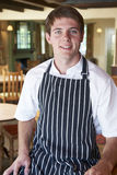 Chef Wearing Whites And Apron Sitting In Restaurant. Portrait Of Chef Wearing Whites And Apron Sitting In Restaurant Stock Photo