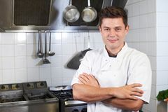 Portrait Of Chef Wearing Whites Standing By Cooker In Kitchen. Chef Wearing Whites Standing By Cooker In Kitchen stock photos