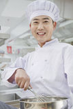 Chef whisking in bowl, portrait Stock Image