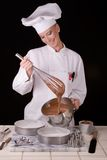 Chef Whisks Cake Batter. Action capture of a smiling female Pastry Chef whisking chocolate devil's food cake batter stock photos