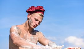 Chef in white hat on strict face, sky on background. Man with muscular torso covered with flour looks attractive. Man. With attractive appearance works as baker royalty free stock photo