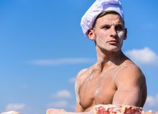 Chef in white hat on strict face, sky on background. Man with muscular torso covered with flour looks attractive. Man. With attractive appearance works as cook stock photos